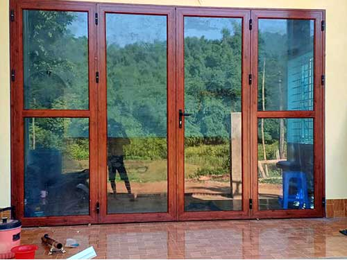 Mẫu cửa nhôm Xingfa 4 cánh giả gỗ kính màu xanh đen